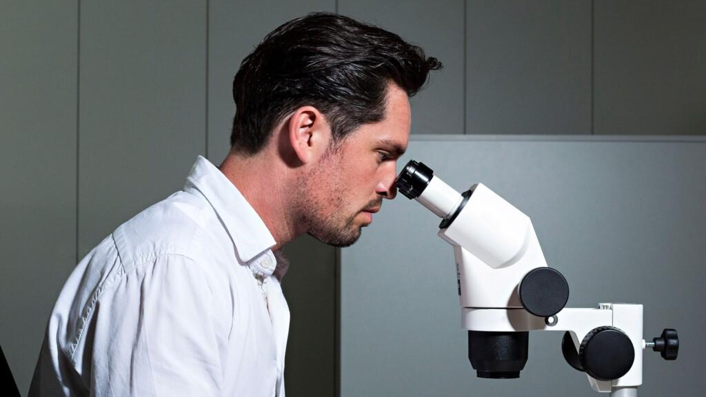 Gemologist using a gemstone grading microscope. Photo courtesy of IGI.
